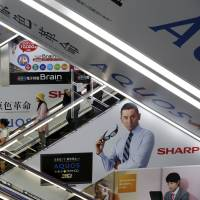 Ads for Sharp products are seen at an electronics shop in Tokyo in 2012. The troubled electronics giant accepted a rescue package by Hon Hai Precision Industry Co. of Taiwan. | REUTERS