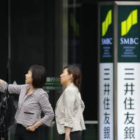 People stand outside a Sumitomo Mitsui Banking Corp. branch in Tokyo in this file photo. | BLOOMBERG