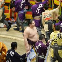 Popular sumo wrestler Endo (center) stands on a ring in Tokyo's Ryogoku Kokugikan on Jan. 24, 2014, before a bout where a winner would gain prized money from companies advertised on banners.   KYODO