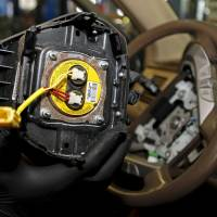 A technician holds a recalled Takata air bag inflator after he removed it from a Honda Pilot at the AutoNation Honda dealership service department in Miami last June. | REUTERS