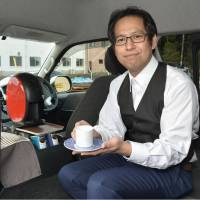 Arita Taxi President Shigetoshi Mieda demonstrates the 'Barista Taxi' on Monday in Arita, Saga Prefecture. | KYODO