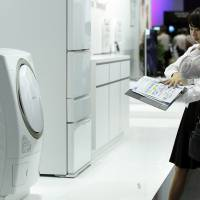An attendant shows off a Toshiba Corp. washing machine to a visitor at the CEATEC Japan exhibition in Chiba Prefecture in October 2014. | BLOOMBERG