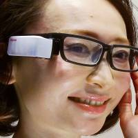 A model demonstrates Toshiba's Wearvue, a glasses-type document displayer that was due to launch on Feb. 29. | KYODO