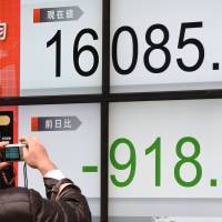 A man takes a photo of a digital stock board showing the Nikkei's 5.4-percent nosedive on Tuesday. The stock average closed at 16,085.44 points. Uncertainty sparked a flight to safe havens such as the yen, Japan government bonds and gold. | AFP-JIJI