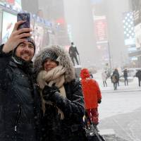 A couple takes a selfie during a snowstorm in the middle of Times Square in the heart of New York City. Impress your date with a spectacular view of the sunset from the best room at the Standard Hotel. | REUTERS