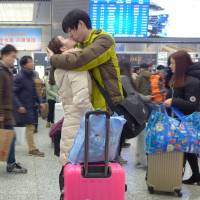 Display of affection: A couple kisses at Hongqiao Railway Station in Shanghai just before departing for  Chinese New Year holidays. Take advantage of the quieter atmosphere this Valentine's Day and sample Shanghai-style dumplings without worrying about crowds. | REUTERS