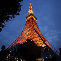 Eiffel of the East: Visitors walk under an illuminated Tokyo Tower at night. Going off the beaten track, skip dinner for two in the city and take your date for an overnight trip to the nearby hot spring resort town of Hakone for a nature-filled Valentine's Day. | BLOOMBERG