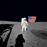 Edgar Mitchell stands beside a U.S. flag after landing on the moon on Feb. 5, 1971. | REUTERS