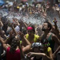 People cool off in water during the 'Escravos da Maua' block party, as part of pre-Carnival celebrations in Rio de Janeiro on Sunday. Merrymakers are taking to the streets in hundreds of open-air 'bloco' parties, before the start of the city's over-the-top Carnival, which officially starts the first week of February, the highlight of the year for many residents. | AP