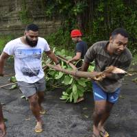 Men clear a fallen tree off a road in Fiji's capital, Suva, on Sunday after Cyclone Winston swept across Viti Levu Island. | REUTERS