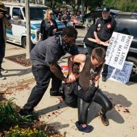Counter-protesters scuffle with a KKK member (on the ground, face hidden) as he stabs an attacking protester during an anti-immigration rally at Pearson Park in Anaheim, California, on Saturday. | AP
