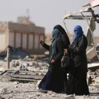 Women walk in the war-ravaged town of al-Shadadi in Hasaka province, northeast Syria, on Friday. | REUTERS