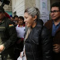 Gabriela Zapata is escorted out of a police station to the prosecutors' office in La Paz on Saturday. | AP