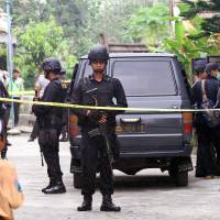 Indonesian police officers stand guard outside the house of a suspected militant following a raid in Malang, Indonesia, on Saturday. | AP