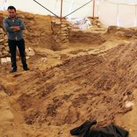 A worker stands at the site near Cairo where archaeologists found a funerary boat. | AFP-JIJI