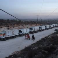 A convoy of aid vehicles heads to the government-held Shiite towns of Fuaa and Kafraya in northwestern Idlib province on Wednesday during an operation in cooperation with the U.N. to deliver aid to thousands of besieged Syrians. | AFP-JIJI