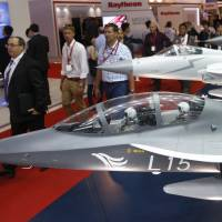 Visitors pass models of fighter jets manufactured by China National Aero Technology Import and Export Corp. during the Singapore Airshow at Changi Exhibition Center on Wednesday. | REUTERS