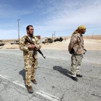 Libyan soldiers man a checkpoint in Wadi Bey, west of the Islamic State-held city of Sirte, Feb. 23. An Islamic State convoy was believed wiped out by an airstrike near Sirte on Sunday. | REUTERS