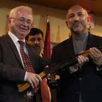 Russian Ambassador to Afghanistan Alexander Mantytskiy (left) hands over an AK-47 rifle to Afghan National Security Adviser Hanif Atmar during a ceremony at a military airfield in Kabul on Feb. 24, 2016. Russia delivered 10,000 Kalashnikovs to the Afghan government on the same day, with officials saying they were for the fight 'against terrorism.' | AFP-JIJI