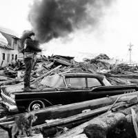 A photographer looks over wreckage in March 1964 as smoke rises in the background from burning oil storage tanks at Valdez, Alaska. On Monday, federal scientists say they've pinpointed the cause of tsunami following the 1964 Great Alaska Earthquake, the second-largest ever recorded, at magnitude-9.2. | AP