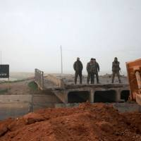 Syrian government forces look at a bridge broken by Islamic State group fighters connecting the village of al-Tiba with Aleppo's thermal power plant on the eastern outskirts of the Syria's northern embattled city of Aleppo after they retook the area Monday. | AFP-JIJI