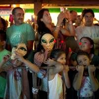 Tourists watch a parade during the annual Alien Festival on Saturday in Capilla del Monte, Argentina, the site of an alleged UFO sighting 30 years ago. | AP