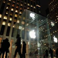 People walk outside the Apple store on  Fifth Avenue in New York on Wednesday. Apple's challenge of a court order to unlock an iPhone used by one of the San Bernardino killers opens up a new front in the long-running battle between technology companies and the government over encryption. | AFP-JIJI