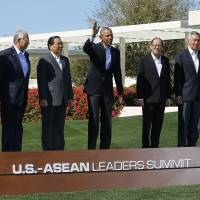 U.S. President Barack Obama waves as he is flanked by some of the leaders from the 10-nation Association of Southeast Asian Nations (ASEAN) summit during a group photo in Rancho Mirage, California, on Tuesday. | REUTERS