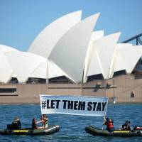 Members of the environmental group Greenpeace mount a protest in Sydney on Sunday. A hospital in Brisbane has refused to send an asylum-seeker baby back to detention in Nauru as momentum builds across the country against offshore camps. | AFP-JIJI
