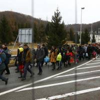 Migrants walk toward the Austrian border town of Spielfeld in the village of Sentilj, Slovenia, Tuesday. | REUTERS