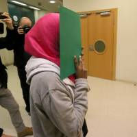 A 17-year-old Swedish woman who is suspected to be an Islamic State supporter arrives for the start of her trial at the main court in Vienna Thursday. Austrian authorities said Thursday they are probing four men in custody over their links to the November Paris attacks. | AP