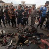 Iraqis inspect the damage at the site of a bombing claimed by the Islamic State group near a market in the Sadr City area of northern Baghdad, on Sunday. Islamic State also attacked an army position west of Baghdad, temporarily holding it and killing at least eight security personnel over the course of the day. | AFP-JIJI