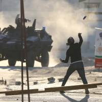 A protester throws a glass bottle containing paint at a riot police armored personnel carrier during anti-government clashes in the village of Sitra, south of Manama, Sunday. Protesters took to streets in Bahrain on Sunday to mark the fifth anniversary of the 2011 uprising. | REUTERS