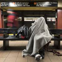 A man rests under a blanket while sitting on a bench in a New York subway station Tuesday. Researchers from Weill Cornell and scientists at the American Museum of Natural History have traced bedbugs through the city's subway system and discovered a genetic diversity among the bloodsucking creatures. | AP
