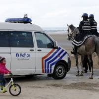 A girl cycles past Belgian police officers on horses in the coastal town of Zeebrugge Wednesday after Belgium set up border checks along its frontier with France to avoid migrants bound for Britain choosing the country as a transit point, as a large camp near the French city of Calais is set to be cleared, Belgium's interior minister said. | REUTERS