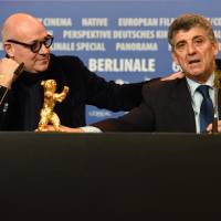 Pietro Bartolo (right), director of a hospital on the Italian island of Lampedusa, and Italian director Gianfranco Rosi, who was awarded the Golden Bear for best film for the documentary 'Fire at Sea,' attend a news conference after the awards ceremony in Berlin on Saturday. | AFP-JIJI