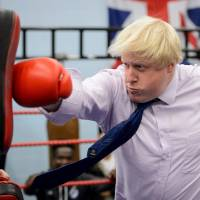London Mayor Boris Johnson boxes with a trainer during his visit to the Fight for Peace Academy in North Woolwich, London, in October 2014. | AFP-JIJI