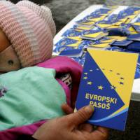 A volunteer holds up a mock European passport during a campaign by the Center for Promotion of Civil Society in Sarajevo on Dec. 21, 2010. | REUTERS