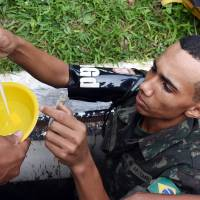 A member of the Brazilian armed forces looks for larvae of the Aedes aegypti mosquito, which transmits dengue and Chikungunya fever and Zika virus, at a school in Brasilia on Friday, when the government held a national day of mobilization against the Zika virus to raise awareness among teachers, students and school officials about the need to eliminate breeding grounds of the mosquito. | AFP-JIJI