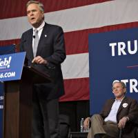 George W. Bush, former U.S. president, listens as his brother, Jeb, former governor of Florida and 2016 Republican presidential candidate, speaks during a campaign event in Charleston, South Carolina, Monday. | BLOOMBERG