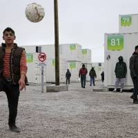Migrants play soccer amid shipping containers converted into homes at a state-run shelter near Calais, northern France, Sunday. The shelter is meant to be a replacement for a camp for migrants called the 'jungle' near Calais, and French authorities have asked migrants staying in the south of the 'jungle' to leave before Tuesday. | REUTERS
