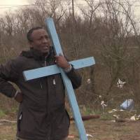 In this frame grab from APTN taken on Monday, the Rev. Teferi Shuremo holds a cross and watches as a makeshift church is destroyed at a migrant camp in Calais, France. A regional official said the operation Monday was the culmination of a two-week effort to clear a 100-meter security zone around the perimeter of the camp. | AP
