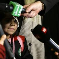 Falak al Hourani, 7, who has a rare form of eye cancer, stands beside her mother, Yasmina, as they are interviewed by journalists upon their arrival at Rome's Fiumicino international airport Thursday. | AP