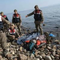 Turkish paramilitary police collect the dead body of a migrant from the beach near the Aegean town of Ayvacik, Canakkale, Turkey, Saturday. A boat carrying migrants to Greece hit rocks off the Turkish coast on Saturday and capsized, killing at least 33 people, including five children, officials and news reports said. Some 75 other migrants were rescued. | AP