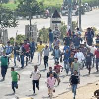 Protestors run along a street during violence after rival caste groups clashed during a mass rally over access to jobs and education in the district of Rohtak, in northern India, on Friday. | AFP-JIJI