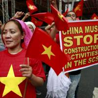 Protesters waving Vietnamese flags outside the Chinese Consulate in the city of Makati, in Metro Manila, denounce China's military buildup in the South China Sea on Thursday. | REUTERS