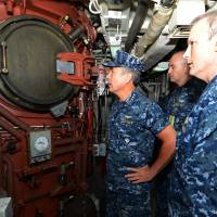 Adm. Harry Harris (left) examines missile tubes aboard the submarine USS Louisiana in this 2014 file image. | U.S. NAVY