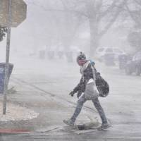 A woman walks into the wind as snow begins to fall and visibility quickly drops Wednesday in Bourbonnais, Illinois. A powerful storm moving through parts of the Midwest on Wednesday could dump more than a foot of snow in places. | AP
