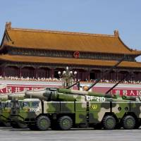 Chinese military vehicles carrying DF-21D anti-ship ballistic missiles, potentially capable of sinking a U.S. Nimitz-class aircraft carrier in a single strike, travel past Tiananmen Gate during a military parade to commemorate the 70th anniversary of the end of World War II in Beijing, in September. China will likely announce another large rise in defense spending next month, as the ruling Communist Party seeks to assuage the military's unhappiness at sweeping reforms and as worries over the South China Sea and Taiwan weigh on Beijing. | ANDY WONG / POOL / FILES / CHINA-DEFENSE / REUTERS
