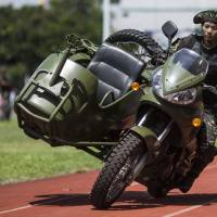 A Chinese People's Liberation Army soldier performs a motorcycle stunt during a demonstration for the public at the Ngong Suen Chau Barracks in Hong Kong last July. | BLOOMBERG